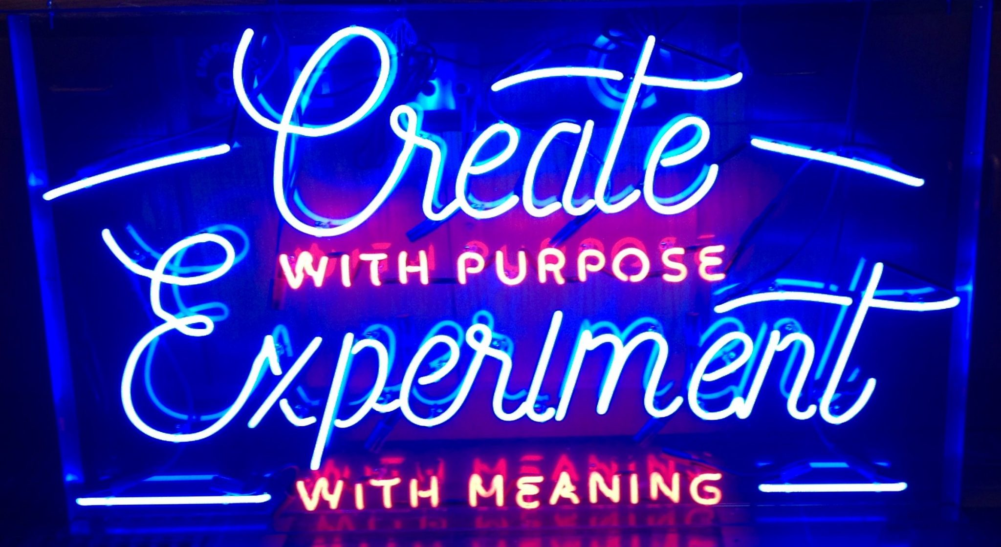 neon sign says create purpose experiment meaning