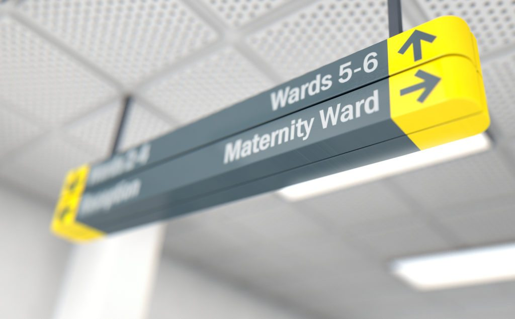 A ceiling mounted hospital directional sign highlighting the way towards the maternity ward - 3D render