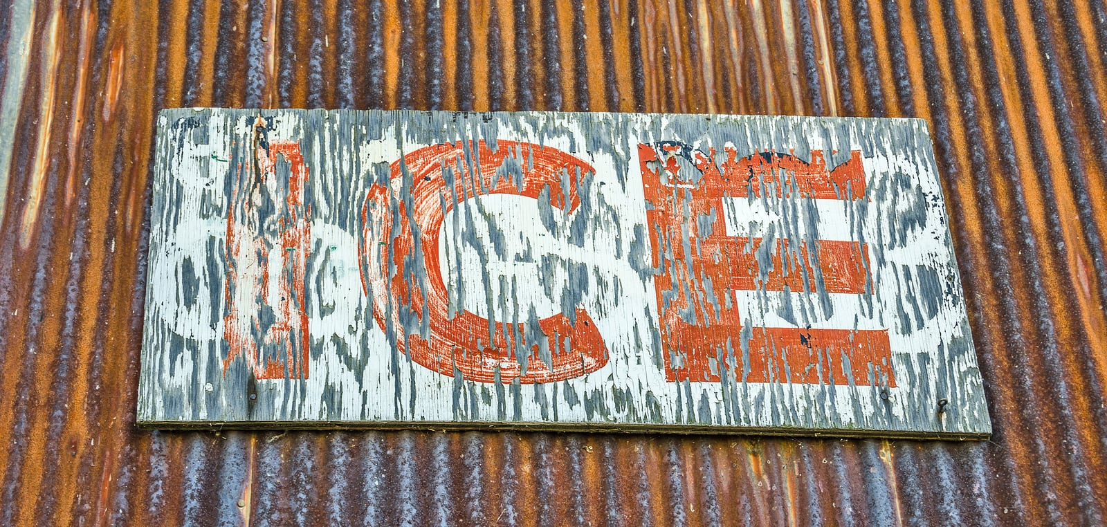 Rust on the corrugated metal and weathering of the wood sign for ice