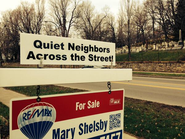 "For sale sign next to cemetery that says ""quiet neighbors across the street"""